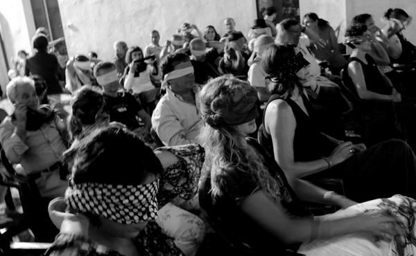 Pubblico seduto e bendato durante il concerto